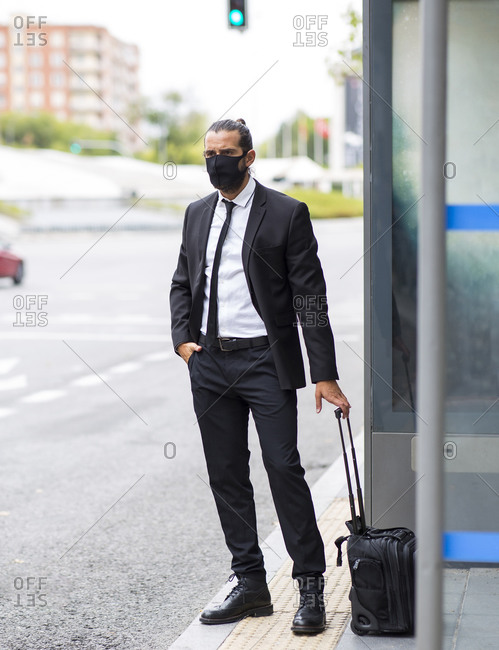 Businessman wearing protective face mask waiting at bus stop with suitcase
