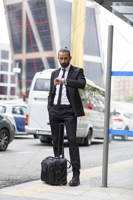 Bearded businessman checking time while waiting at bus stop