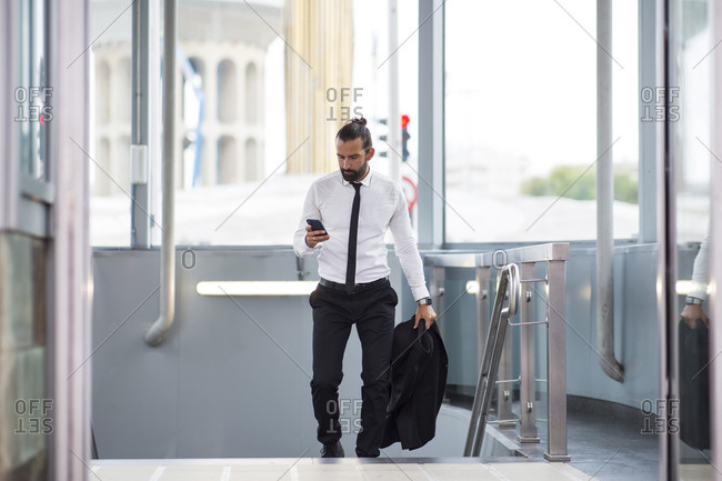 Businessman walking up stairs with smart phone in hand
