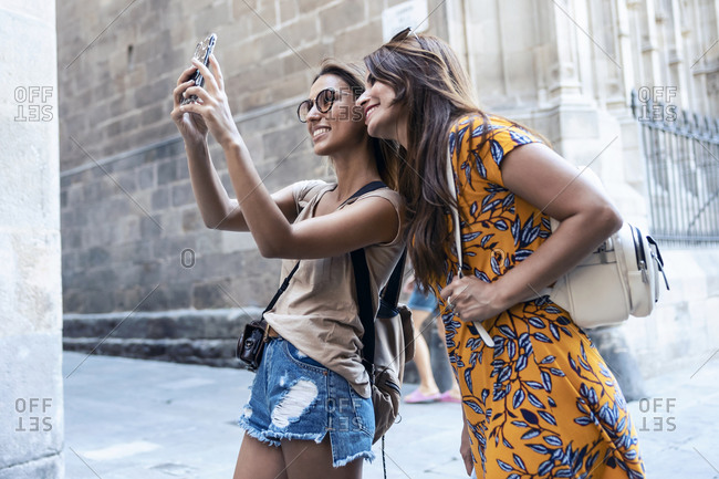 Friends taking selfie through mobile phone while standing at Gothic Quarter- Catalonia- Spain