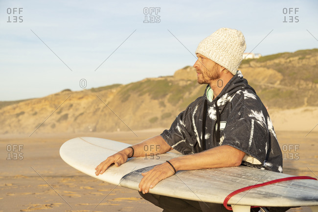 Man looking away while crouching with surfboard at beach