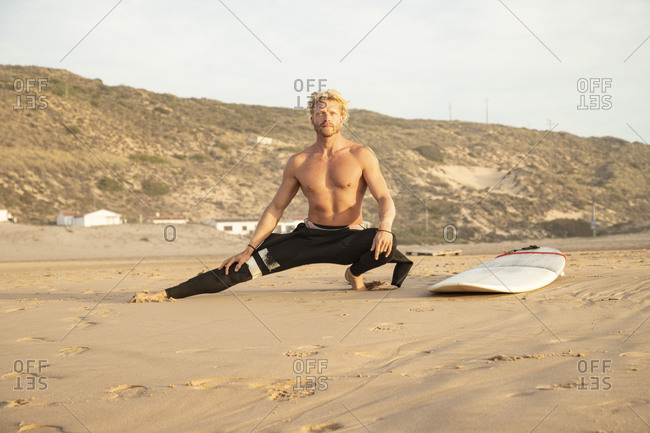 Shirtless man stretching by surfboard on sand at beach
