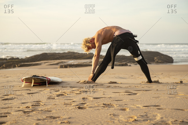 Shirtless male surfer exercising by surfboard at beach