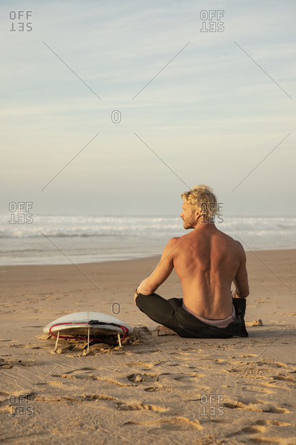 Shirtless surfer sitting by surfboard on sand while looking at sea against sky