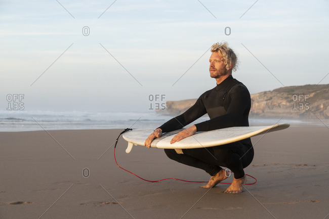 Blond surfer with surfboard on lap crouching at beach against sky
