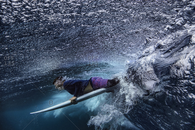 Male surfer with surfboard on wave undersea