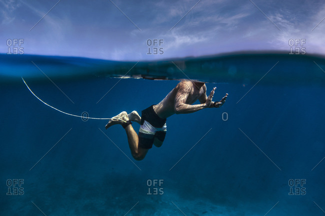 Shirtless surfer with surfboard leash swimming undersea at Maldives