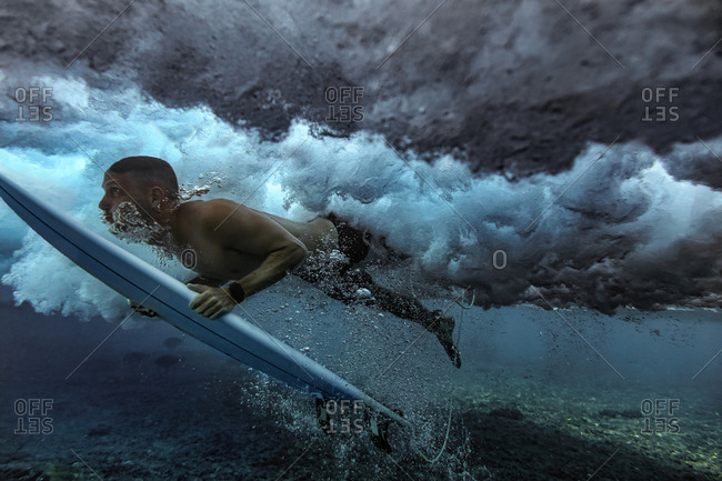Male surfer duck diving in water with surfboard at Maldives