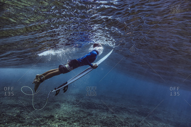 Male surfer holding surfboard while diving undersea at Maldives