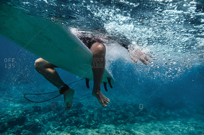 Male surfer sitting on surfboard while surfing in sea at Maldives