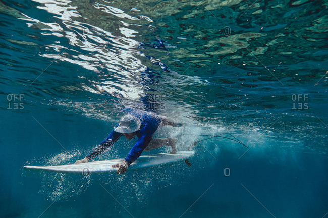Male surfer diving with surfboard in sea at Maldives
