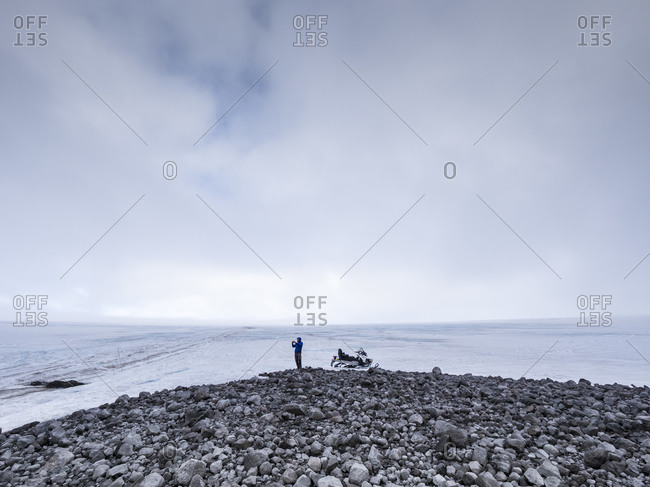 Male tourist exploring while standing on land against cloudy sky- Langjokull- Iceland