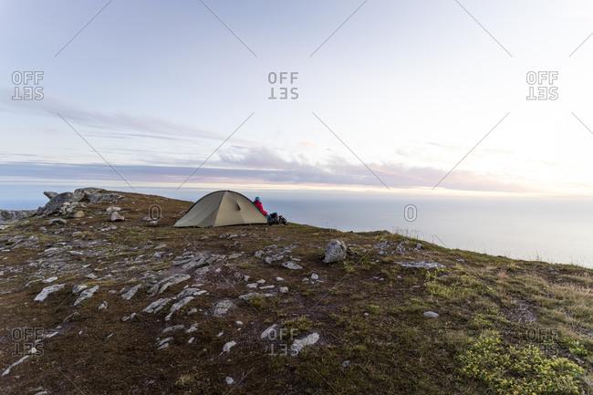 Woman sitting by tent on mountain at Ryten- Lofoten- Norway