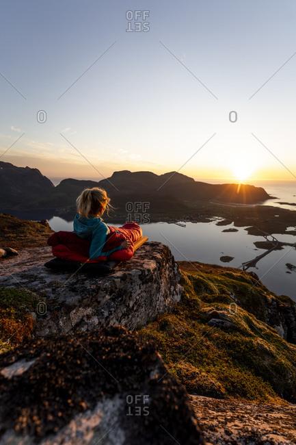 Woman admiring sunset view while lying in sleeping bag at Volandstinden- Lofoten- Norway