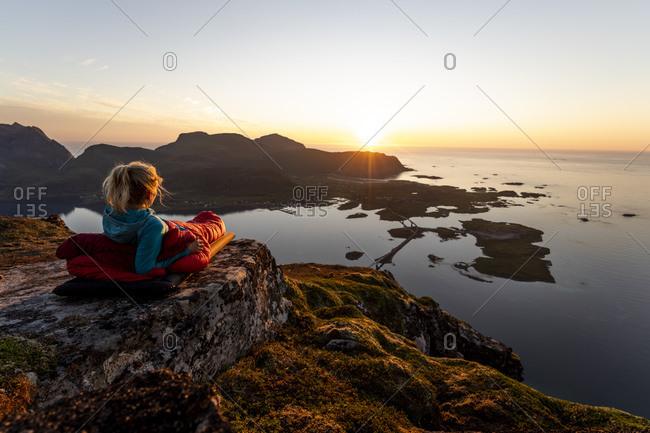Hiker admiring sunset view while lying in sleeping bag at Volandstinden- Lofoten