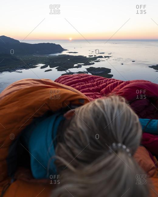 Woman lying in sleeping bag against sea at Volandstinden- Lofoten- Norway