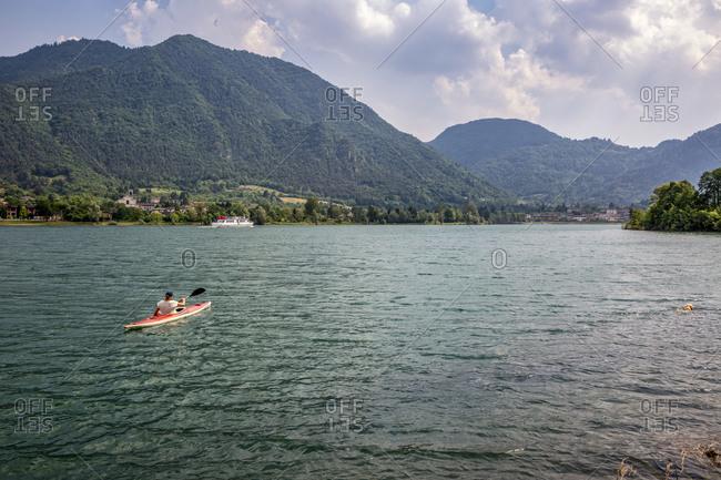 Active senior man kayaking on Lake Idro against cloudy sky