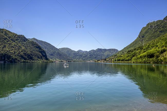 Idyllic view of Lake Idro and mountain against blue sky