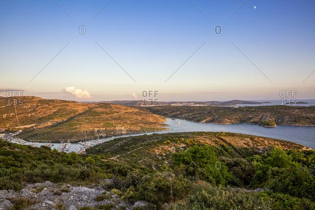 Croatia- Sibenik-Knin County- Primosten- Clear sky over harbor of coastal town at dusk