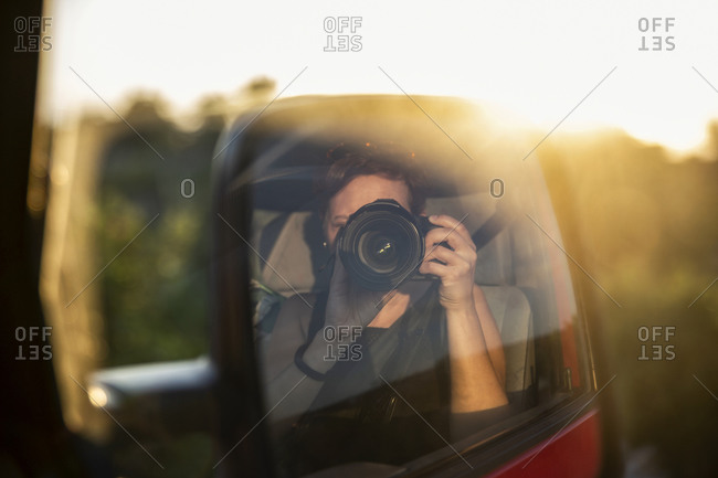 Side-view mirror reflection of woman photographing setting sun