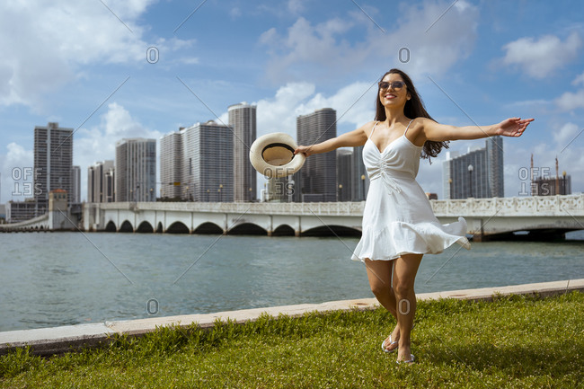Happy young woman spinning on grass by bay against sky