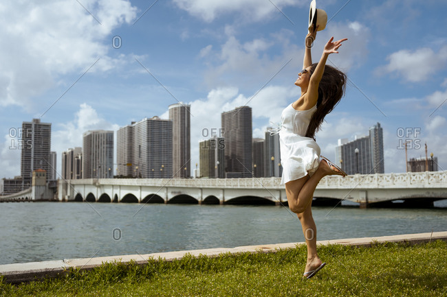 Excited female tourist jumping over grass by bay