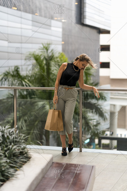 Mid adult woman with shopping bag looking down while standing by railing