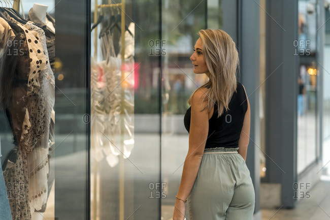 Woman doing window shopping while standing by store window