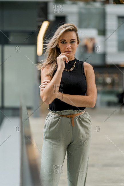Woman with hand on chin staring while standing by railing