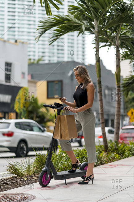 Woman using mobile phone while standing with push scooter and shopping bag on footpath