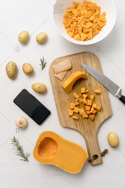 Studio shot of smart phone- raw potatoes- and cutting board with chopped squash