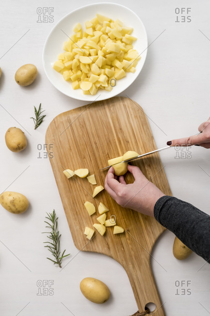 Hands of woman chopping potatoes on cutting board