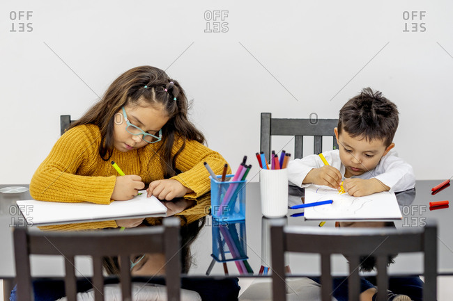Brother and sister learning drawing while sitting in living room