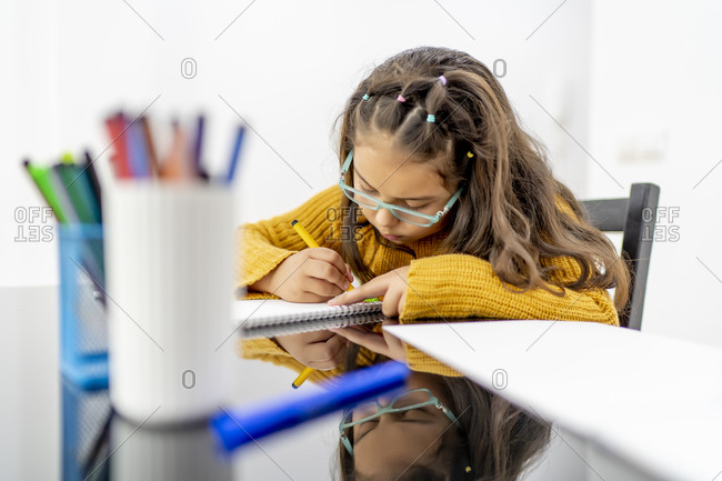 Girl drawing in book on table at home