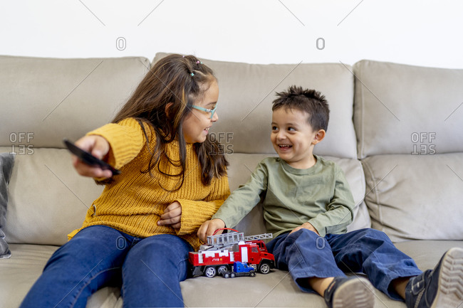 Happy siblings sitting on sofa watching TV at home