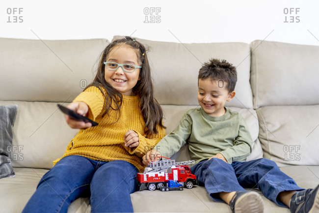 Sister watching TV while brother playing with fire engine toy on sofa at home