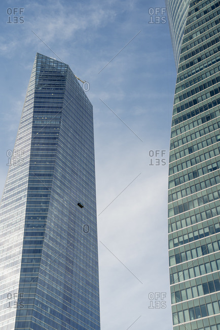 Spain- Madrid-Window cleaners platform hanging from tall modern skyscraper