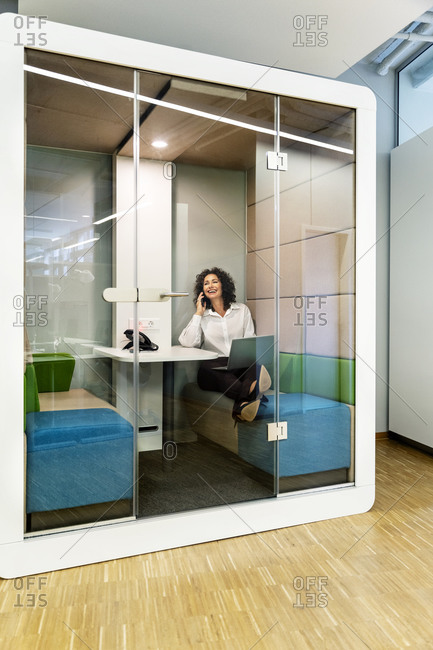 Businesswoman with laptop talking on mobile phone while sitting in cabin at office