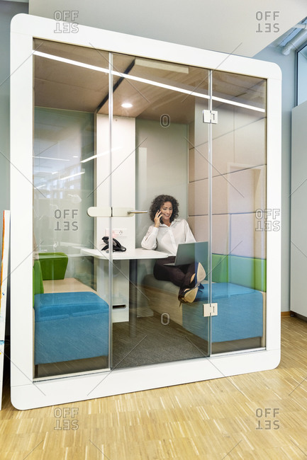 Businesswoman talking on mobile phone while working on laptop sitting in cabin at office