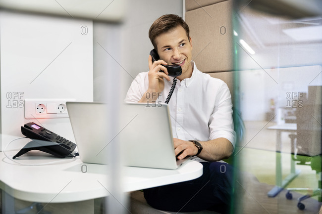 Businessman smiling while talking on telephone sitting at office