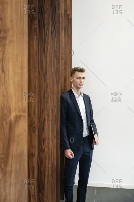 Businessman with digital tablet leaning on wooden wall