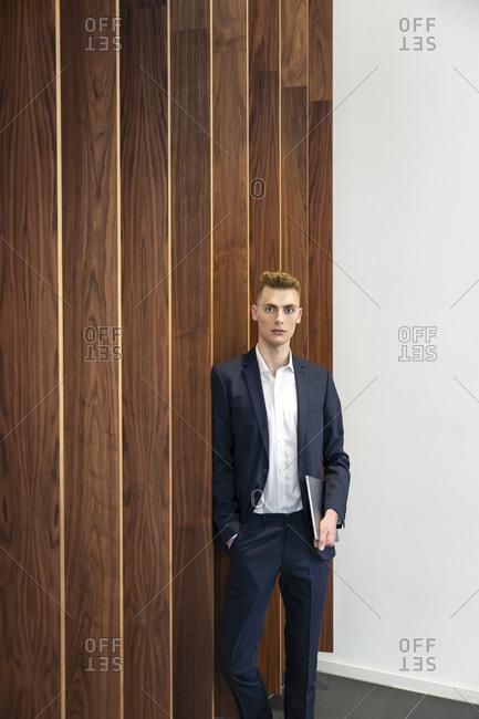 Confident entrepreneur holding digital tablet leaning on wooden wall