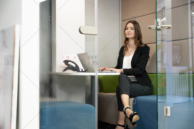 Confident businesswoman using laptop while sitting in cabin at office
