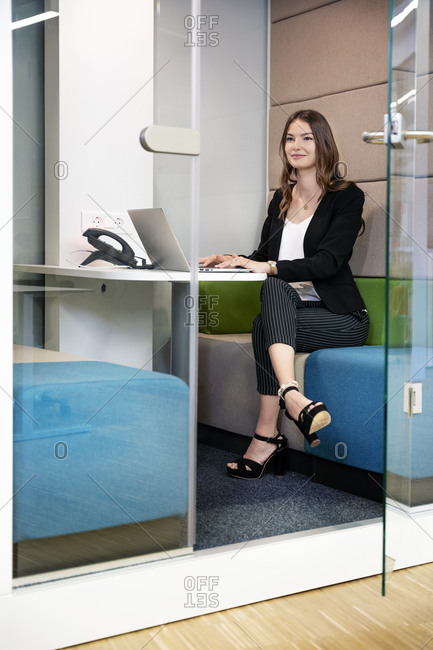 Smiling businesswoman using laptop while sitting in cabin at office