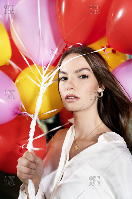 Young businesswoman staring while holding multi color balloon at office