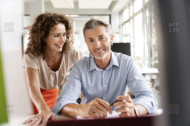 Businesswoman looking at man while sitting at office