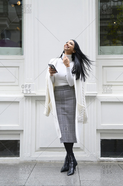 Cheerful businesswoman with mobile phone looking up while standing against wall