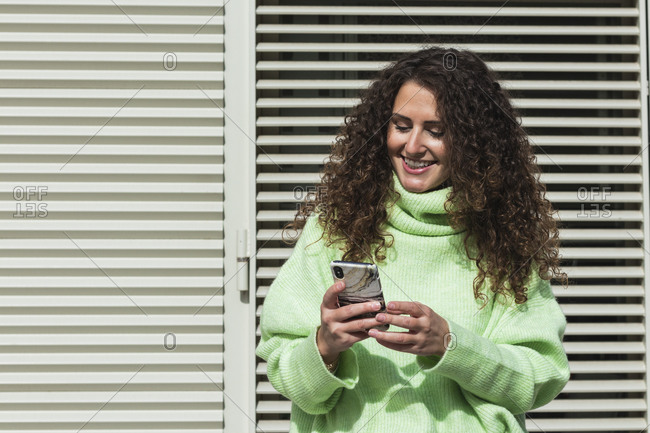 Smiling woman in neon green sweater using mobile phone against metallic door on sunny day