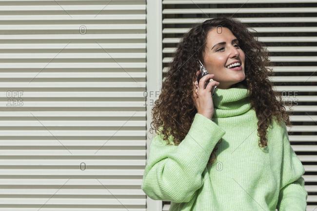 Smiling woman in neon green sweater talking on mobile phone against metallic door