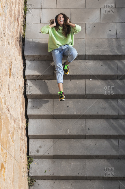 Cheerful woman enjoying music through headphones while sitting on staircase